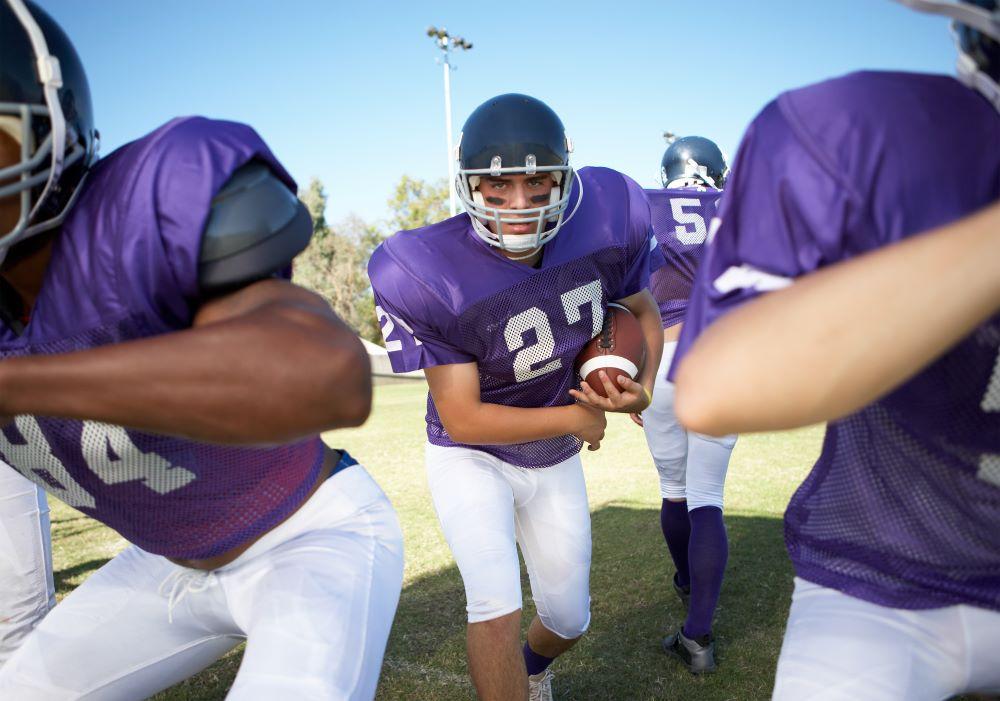 highschool football running back carrying the ball