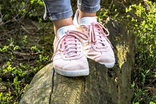 pink shoes walking on log
